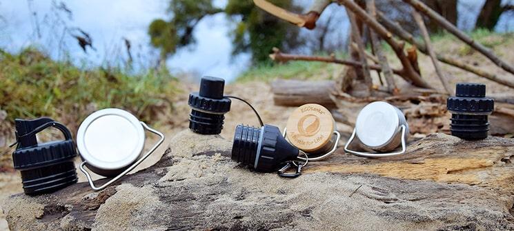 Bild der ECOtanka Edelstahl Fachverschluss mit Bambusplättchen aus nachhaltigem Anbau und Tragebügel, Edelstahl Wave Verschluss mit Tragebügel, Adapter Verschluss, Sport-Verschluss mit Staubkäppchen, Reduzier Verschluss mit 2cm Trinköffnung und Verschlusskäppchen, Poly-Loop-Verschluss mit Karabinerhaken aus PP5 in schwarz. Für die Edelstahl Trinkflaschen 0,35l bis 2,0l. Platziert auf einem Baumstamm.