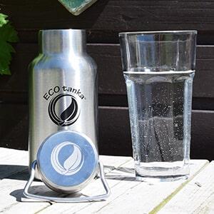 Bild der 350ml doppelwandig isolierenden Trinkflasche aus Edelstahl in Silber von ECOtanka mit Edelstahl-Wave-Verschluss und einem Edelstahl-Tragebügel. Für einen leichten Transport der Warm-, Heiß- oder Kaltgetränke. Heißes bleibt lange heiß – kaltes länger kalt. Auf einem Holztisch mit einem Glas Wasser