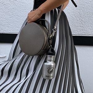 Bild der 350ml einwandigen Trinkflasche aus Edelstahl in Silber von ECOtanka mit Poly-Loop-Verschluss in schwarz aus PP5 und Karabinerhaken. Ideal für die Befestigung an Rucksäcken und Taschen. Der Kompakte Begleiter für klein und groß. An einer Handtasche befestigt.