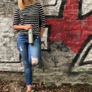 Frau mit Edelstahl Trinkflasche an der Wand